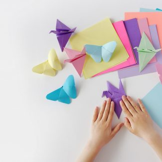 Children's hands do origami from colored paper on white background. lesson of origami; Shutterstock ID 1100575436; Purchase Order: AD039